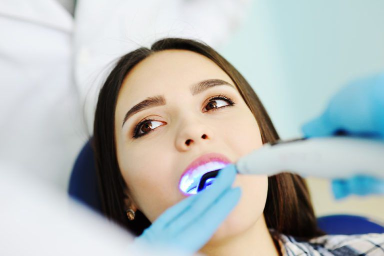 Woman at the dentist, receiving dental sealants