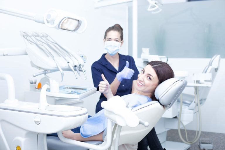 Female dentist in blue scrubs giving a thumbs up standing behind a female patient sitting in slightly reclined dental chair smiling and giving a thumbs up