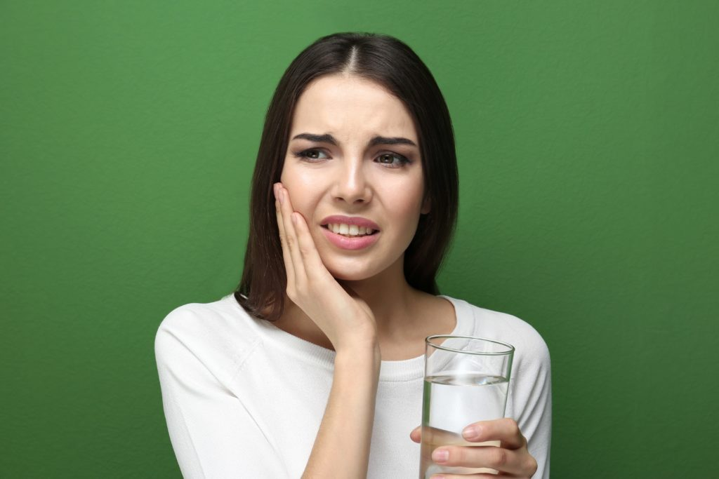Brunette woman on green background holding a glass of water and one hand and her cheek in the other with a pained expression