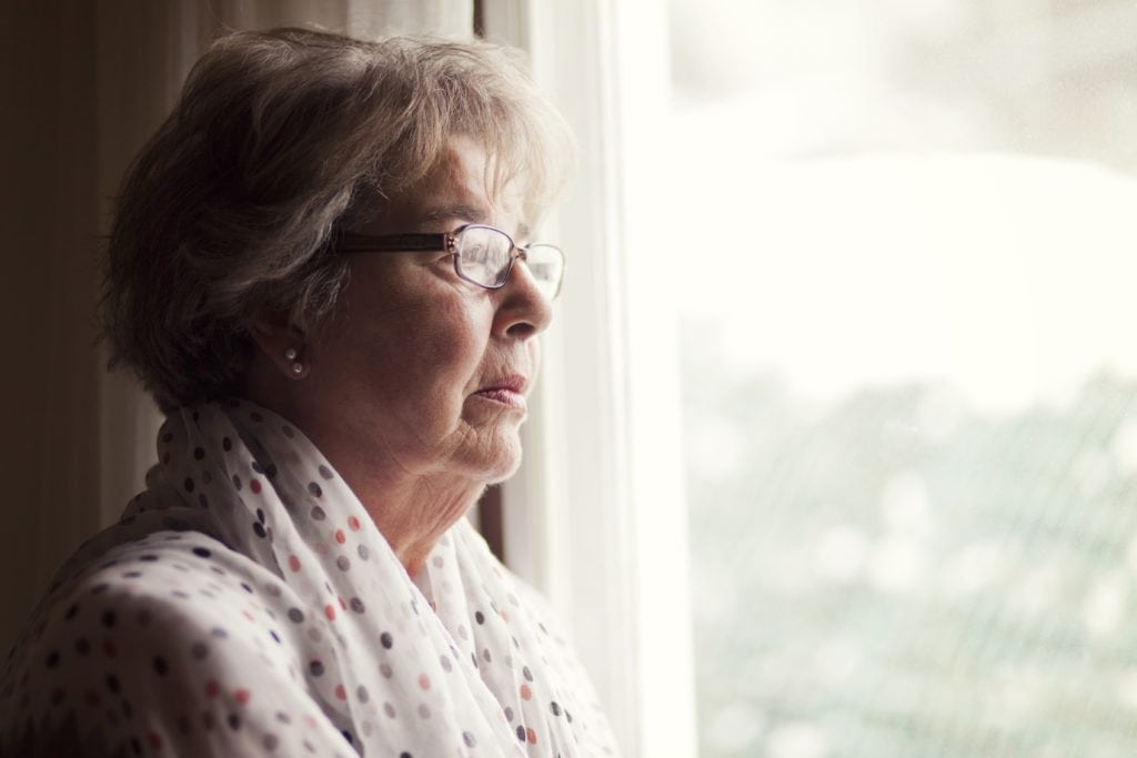 Senior woman looking longingly out the window