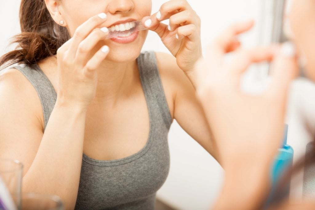 Woman looking in the mirror and applying whitestrips